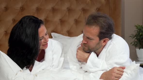Thumbnail for Mature Married Couple in Bathrobes Talking, Lying in Bed at the Hotel Together