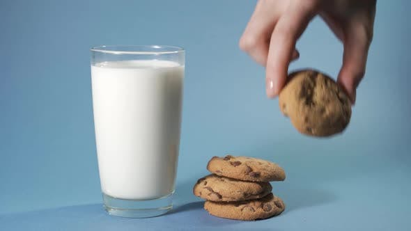Cover Image for Female Hand Dipping Cookies in Milk