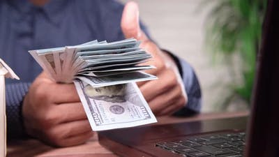 Concept of House Finance with Young Man Holding Cash