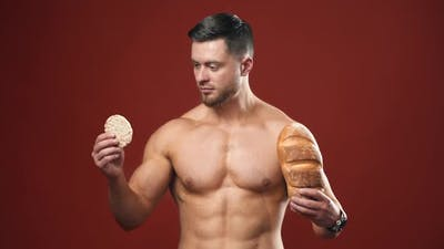Healthy food choices. Naked sportsman choosing between healthy and unhealthy bread