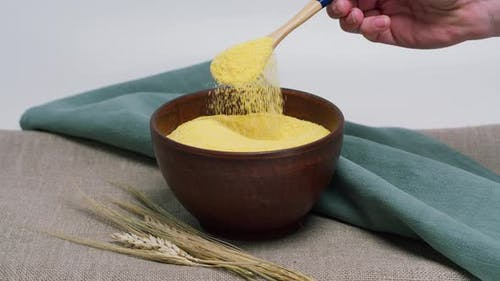 Falling Polenta From Wood Spoon Into Bowl