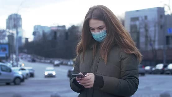 Thumbnail for Portrait of Worried Woman Standing on City Street in Protective Mask and Using Smartphone. Busy