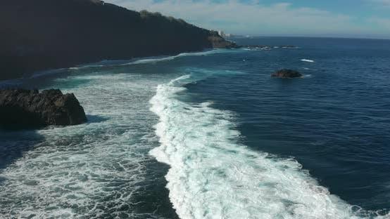 Aerial Top View Waves Break on Dark Rocks Near Beach