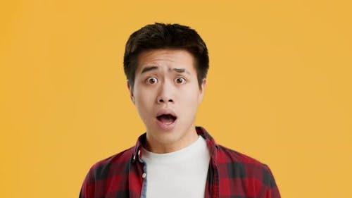 Shocked Asian Guy Looking At Camera In Surprise Yellow Background