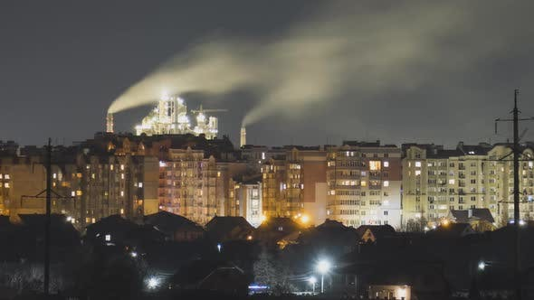 High rise apartment buildings in city residential area and tall factory chimneys with smoke