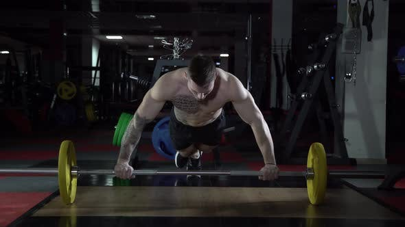 Tattooed Male Athlete Is Pushed Away From the Bar