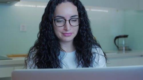 Frau tippt auf Laptop und sitzt zu Hause auf dem Sofa, Geschäftsfrau sitzt zu Hause auf dem Smartphone