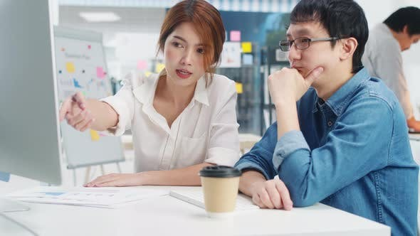 Japanese male boss supervisor teaching intern or new employee korean girl with difficult assignment.