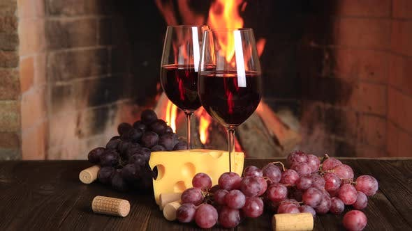 Thumbnail for Two Glasses of Red Wine with Cheese and Grapes Near the Fireplace.