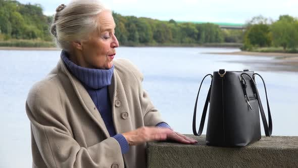 Thumbnail for An Elderly Woman Dances with a Smile - a Lake in the Blurry Background