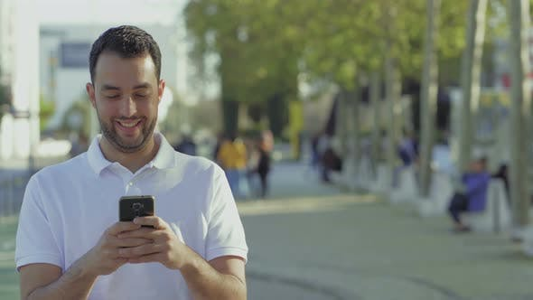 Cover Image for Smiling Young Brunet Using Smartphone Outdoor