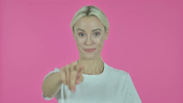 Thumbnail for Young Woman Pointing at Camera on Pink Background