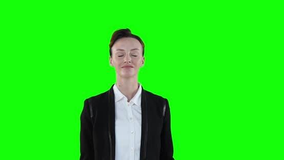 Caucasian woman raising hands on green background