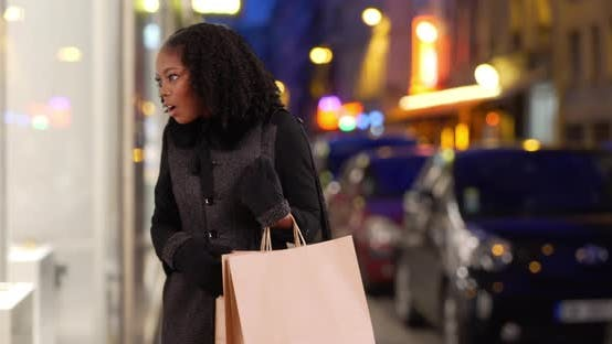 Thumbnail for Pretty black female sees something she likes in elegant store window in evening