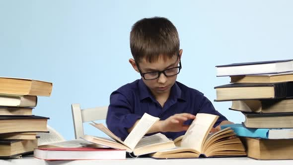 Boy Sits at the Table and Excitedly Leafing Through the Pages of Books. Blue Background.