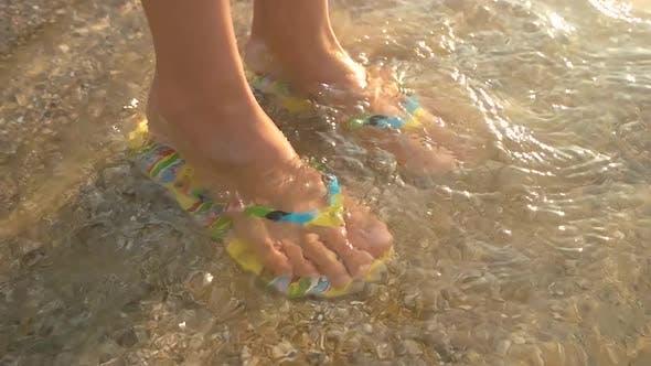Female Feet Wearing Flip Flops.