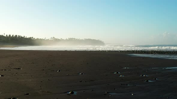 Thumbnail for Moving across a black sand beach at sunrise