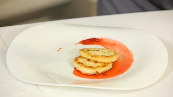 Thumbnail for Putting a Portion of Cottage Cheese Pancakes with Berry Jam on a Plate