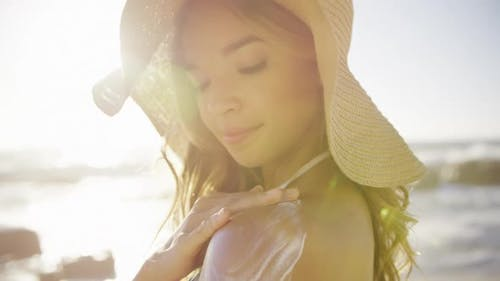 Woman applying sunscreen lotion on the beach
