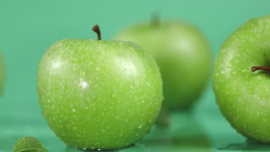 Rotating Fresh Green Apples with Water Drops .