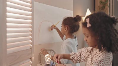 Girls Drawing on Paper on Wall