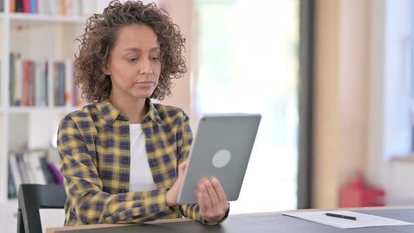 Young Mixed Race Woman Using Digital Tablet at Work