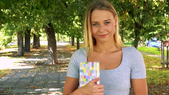 Thumbnail for Young Pretty Blond Woman Holds Book and Smiles - Park with Trees in Background