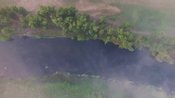 Top-down View Over Little Misty River Streaming Through Valley. Aerial Shot of Beautiful Foggy