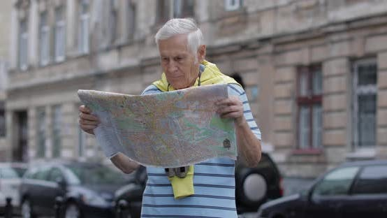 Thumbnail for Senior Tourist Exploring Town with a Map. Looking in Binoculars