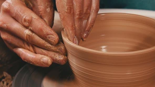 Thumbnail for Mannes Hände Bildhauerei die Seiten aus einem Topf aus dem Ton auf einem Töpferrad