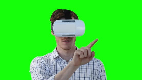 Caucasian man wearing a VR headset on green background