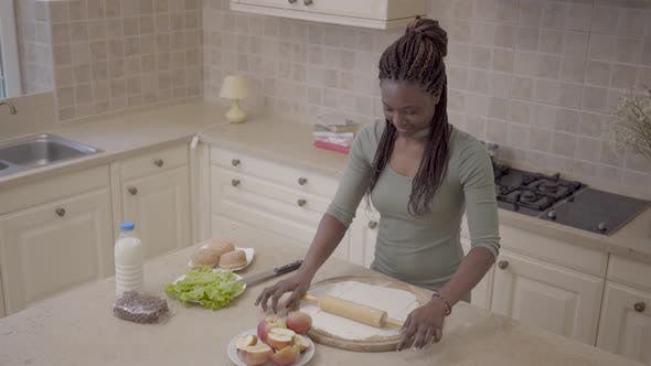 Thumbnail for Beautiful Smiling African American Woman Rolling Dough with Rolling Pin for Apple Pie on the Modern