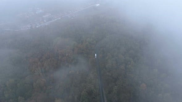 Thumbnail for Top View of White Truck Driving on Dangerous, Misty Forest Road. Drone Chasing White Bus on Foggy