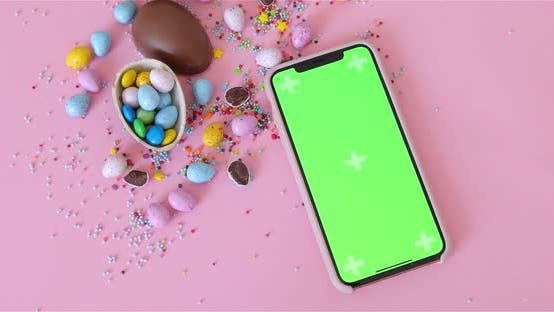 Thumbnail for A heap of chocolate sugar plum candies in colorful glaze isolated on pink background. Iphone 11