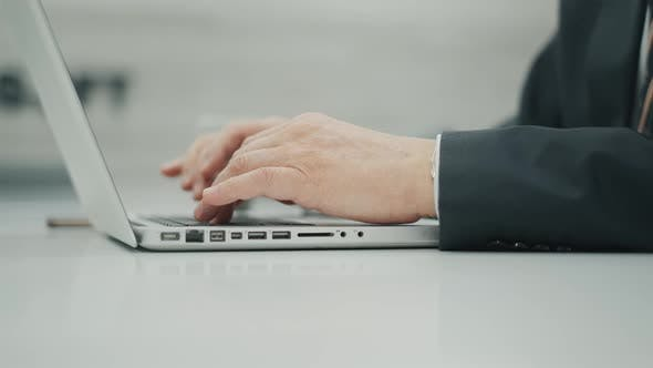 Unrecognizable Senior Man Is Using a Laptop and Typing at the Keyboard. Businessman Is Sitting at