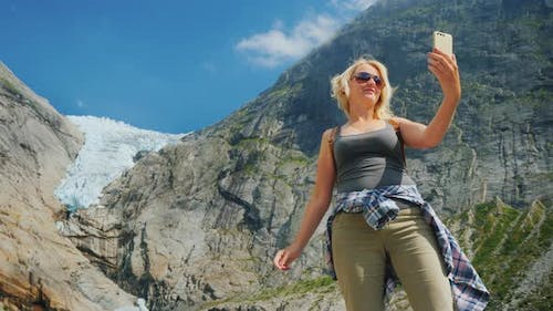 An Attractive Woman Takes a Picture of Herself Against the Background of the Mountains