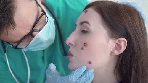 Doctor Examines a Young Woman with Large Moles on Her Face Close Up