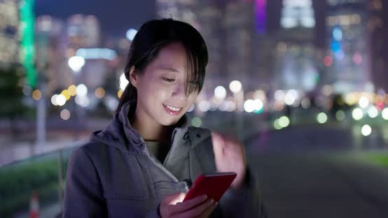 Thumbnail for Woman use of mobile phone at night in city