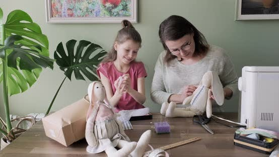Thumbnail for Happy Mother and Daughter Sewing Together Toy Bunny Doll at Home