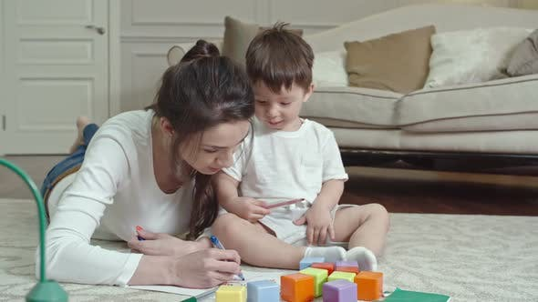 Thumbnail for Cute Child Drawing with Mother
