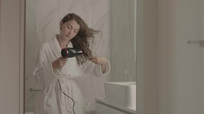 Young Woman Drying Her Hair in Bathroom