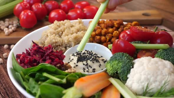 Thumbnail for Eating Vegetable Buddha Bowl Salad With Quinoa And Roasted Chickpeas.