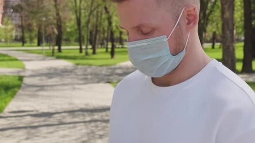 Man in Face Mask Typing on Mobile Phone
