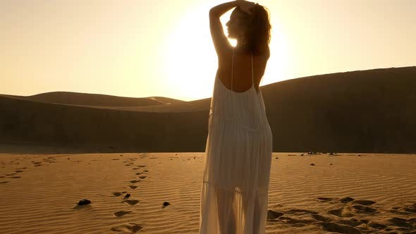 Thumbnail for Beautiful Model Standing with Flare of the Sun in the Background Along the Dunes