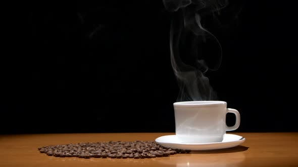 Thumbnail for Hot Coffee Cup and Beans on Wooden Table, Black Background.