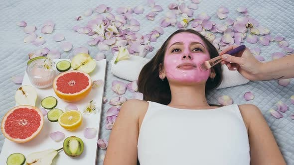Cover Image for Young Woman Relaxing in Wellness Center While Beautician Applying Pink Mask