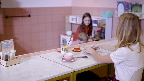Thumbnail for Girl with Mother at Counter in Cafe