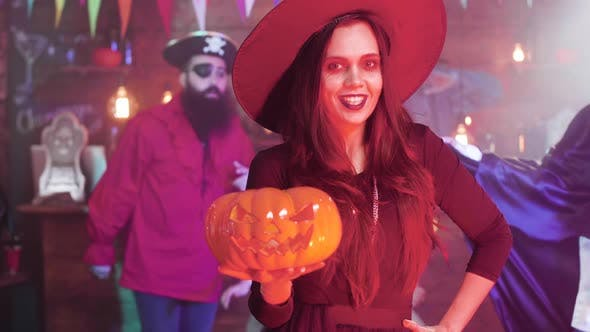 Thumbnail for Young Woman in a Witch Costumes Make a Evil Laugh Holding a Carved Pumpkun