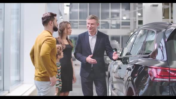 Thumbnail for Confident Male Car Dealer Advertising New Car To the Caucasian Family in Automobile Showroom and