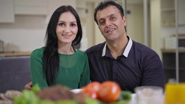 Portrait of Happy Smiling Caucasian Woman and Middle Eastern Man Looking at Camera Sitting at Dinner